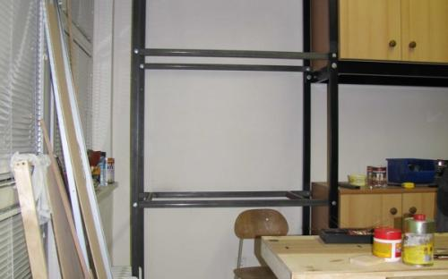 Regálová sestava vedle skříňové stěny u okna
