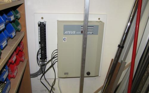 Telefonní centrála již namontovaná na stěně za dveřmi pod kolejištěm