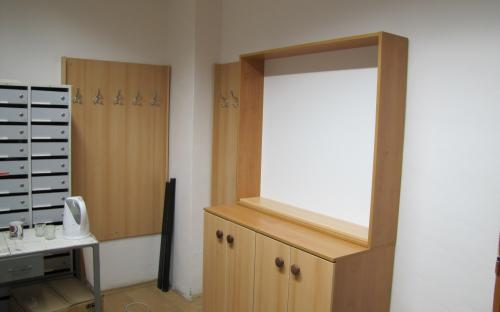 Nové skříňky, vitrína a věšákové stěny v průchozí místnosti