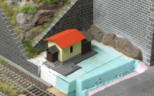 Téměř hotový strážní domek na svém budoucím místě v kolejišti