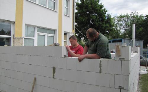 Dělníci zdí obvodovou zeď.
