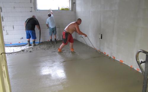 Lití a urovnávání nové betonové podlahy.